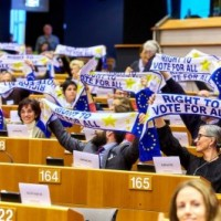 """Στιγμιότυπο από τη συνεδρίαση όπου σύνεδροι σηκώνουν ψηλά κασκόλ με σύνθημα """"Δικαίωμα στην ψήφο για όλους"""""""