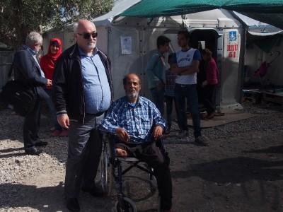 Ο Ιωάννης Βαρδακαστάνης με έναν πρόσφυγα σε αναπηρικό καρότσι