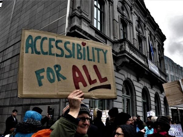 """Φωτογραφία από διαδήλωση στις Βρυξέλλες για την προσβασιμότητα- διαδηλωτής κρατάει αυτοσχέδιο πλακάτ που αναγράφει """"Accessiblity for All"""", Προσβασιμότητα για όλους"""