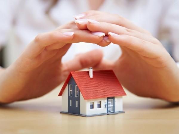 Δύο χέρια προστατεύουν ένα σπίτι